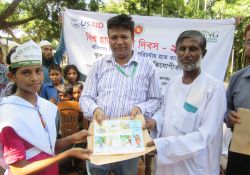 Two men and a woman displaying some children's coloring for Global Handwashing Day