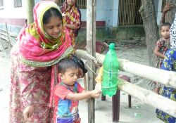 A woman and young child using a tippy tap