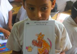 A young boy showing her coloring for Global Handwashing Day
