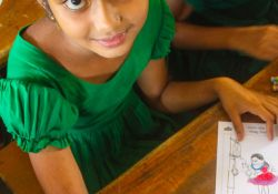 A young girl showing her coloring for Global Handwashing Day