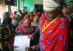 A Community Nutrition Champion works with others at a World Breastfeeding Week event in Narail Sadar upazila
