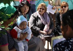 Ambassador Gwaltney watches as SPRING volunteers talk to new mother at her home about the importance of exclusive breastfeeding for the first six months of her child's life.