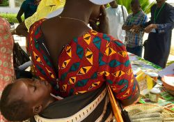A mother listens to learn more about the project's achievements with her baby strapped to her back.