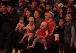 Concertgoers including a few babies sit in rapt attention during a concert.