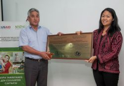 Nora Madrigal, Director of the Health and Education Office, USAID/Kyrgyz Republic, awards a representative from the Shamaldy-Sai General Practice Center with a plaque to certify his health facility as Mother-baby friendly.