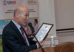 Deputy Minister of Health Madamin Karataev presents a letter of recognition to USAID.