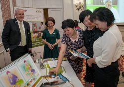 Meeting participants view SPRING materials at the Bishkek closeout event.