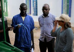A community-based service provider shows USAID staff the agricultural tool that he created after attending a training on the creation of small agricultural tools.