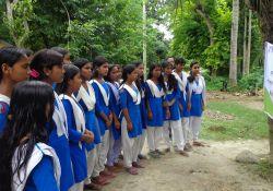 Girls read a roadside banner in Magura district about World Breastfeeding Week