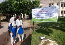 Two school girls stand next to a roadside banner in Abhaynagar upazila