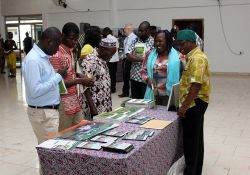 Ziba Dokurugu, SPRING's Agriculture Advisor, receives visitors admiring SPRING's aflatoxin training manuals on display at the event.