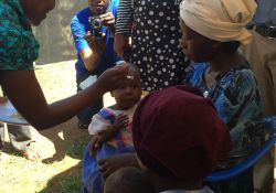 Guest of Honor Dr. Jacent Asiimwe feeds a young child fortified food