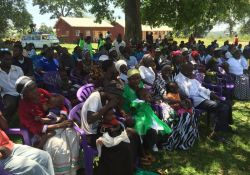 Community members watch from the shade
