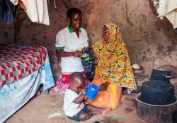 Muwolya, a VHT, shows the mother where to keep the MNP sachet in order for it to remain in good condition.