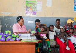 Tendo Nabirye, a mother in a queue at the health facility waiting to receive MNP sachet, as another listens to instructions on how to use MNP from a health worker.