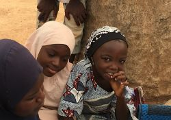 Young girls from the community listen in to an interview with a newly married woman who has regularly participated in support groups since the C-IYCF Counseling Package was initiated in Kajura LGA in July 2015.