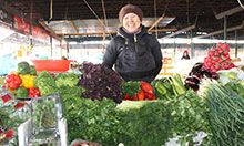 Woman standing at a vegetable stall at market
