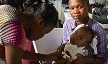 Haiti trainer assessing baby