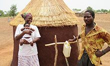 Woman, man, and baby stand outside a hut with a tippy tap