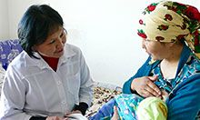 Healthcare worker working with mother holding infant