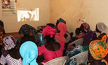 Community members gather to watch a short skit on nutrition and hygiene best practices created by community members.