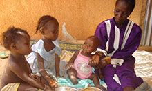 Woman feeding three seated children