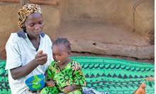 Woman feeding child on her lap.
