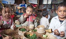 Children sitting and eating at a table in a classroom