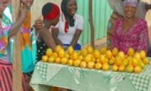 Women sell oranges in a road side market in Ghana.