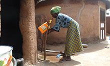 Photo of a woman washing her hands at a tippy-tap.