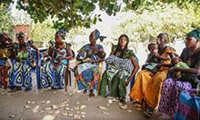 Photo of a group of women sitting on chairs under a tree.