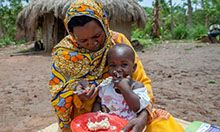 Photo of a woman feeding her child while sitting on a blanket.