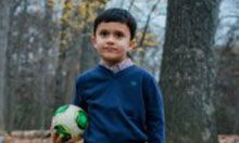 Carrie Malgarejo's son. He is posing in the woods holding a soccer ball.