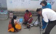 Two people film two women cooking.