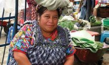 A woman sits next to her stall at a market