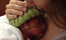 Kristina holds and kisses the head of her premature infant, who has an oxygen tube in his nose.