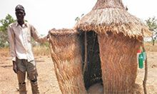 A man stands outside his latrine