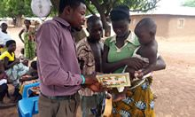 A health worker explains the growth curve of the child to a mother during an outreach service visit.