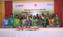 Closeout workshop participants standing in front of a SPRING/Bangladesh banner.