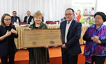 Photo of the group at the BFHI awards ceremony, four people smile and pose holding a large plaque. Caption: At-Bashy FMC is awarded BFHI certification. (pictured left to right) Jarkyn Ibraeva, Deputy Governor of Naryn oblast, Nurgul Ibraeva Senior Specialist of MOH, Nurdin Aliev Director of At-Bashy FMC, and Sadat Sattarova Head of Save the Children International Kyrgyzstan office.