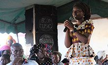 Mariam Sy, SPRING/Senegal Nutrition Advisor, holds a microphone on stage in both hands and addresses the crowd gathered.