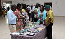 Picture of a group of people looking over a collection of nutrition informational materials on a table.