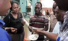 Talian Grain Millers' Production Manager holds up a scoop of fortified maize flour