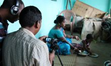 Photo of a film crew working on set with a mother feeding a child.