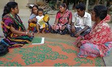 Union Facilitator Oloka Biswas speaks to a farmer nutrition school graduate and her family members.