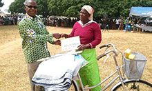 A groundnut farmer receives an award from a FFS instructor.