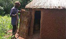 A man stands outside a round latrine structure with a thatched roof.