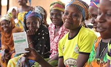 Photo of a woman, Sanatu Fuseini, displaying her VSLA passbook at a meeting with a large group of other women.