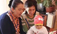 Nurse Usupova Mairam (on the left) counsels Jazgul about the best way to feed her one-year-old daughter Aitunuk.
