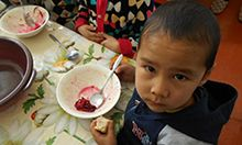 "Photo of a young boy with a bowl of food on the table in front of him. Caption: ""The beet salad is a hit at lunch time!"""